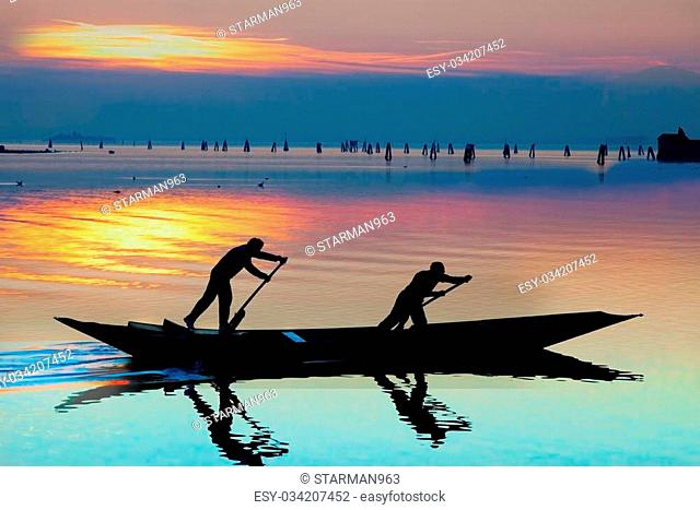 Venice sunset silhouette of sinchronized rowing men on gondola