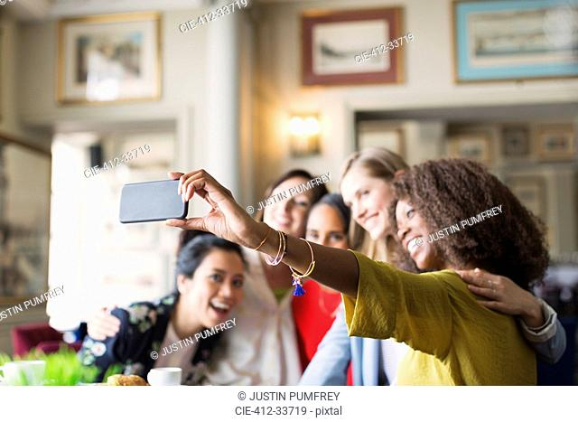 Smiling women friends taking selfie with camera phone in restaurant