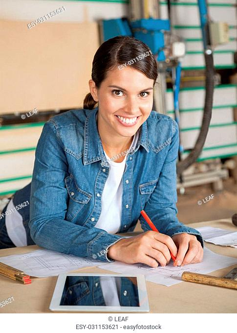 Portrait of confident female carpenter leaning on table in workshop