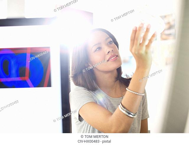 Curious businesswoman examining glass in sunny office