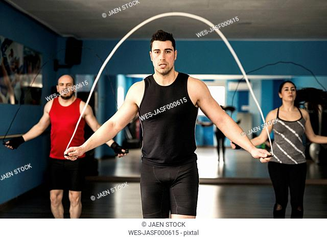 Young people skipping rope in fitness room