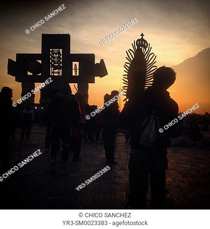 A man holding a sculpture of the Virgin of Guadalupe walks at sunrise during the annual pilgrimage to the Our Lady of Guadalupe basilica in Mexico City, Mexico