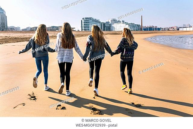 Spain, Gijon, back view of four friends running hand in hand on the beach