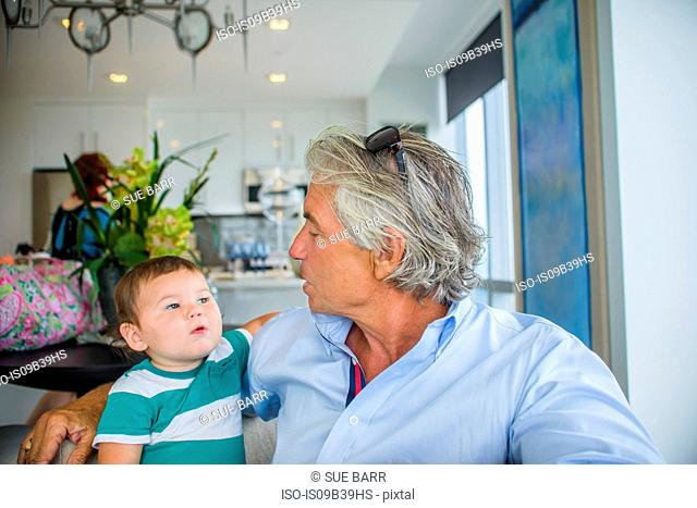 Grandfather chatting with grandson in arms