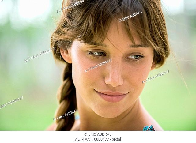 Young woman looking down in thought, portrait