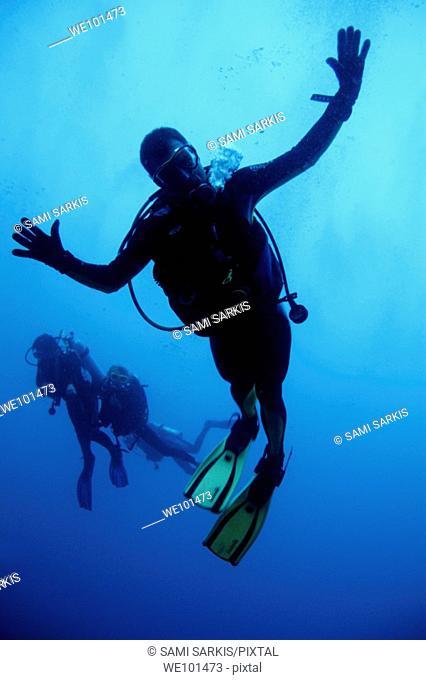 Scuba divers making faces for the camera, Ross Atoll, Maldive Islands