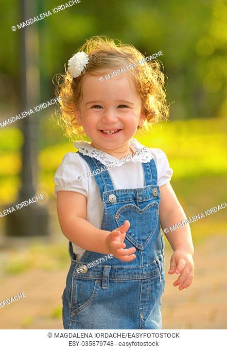 Little girl smiling against the sun