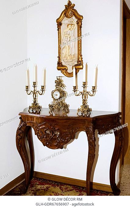Clock and candlestick holders on a table