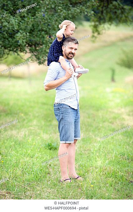 Happy father carrying little daughter on shoulders in nature