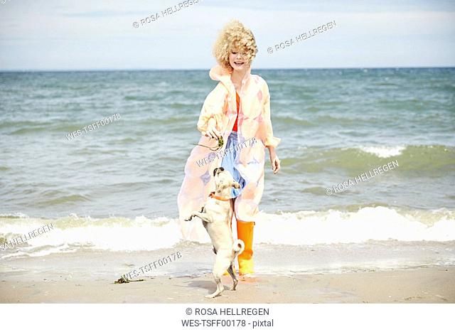 Smiling young woman playing with her dog on the beach