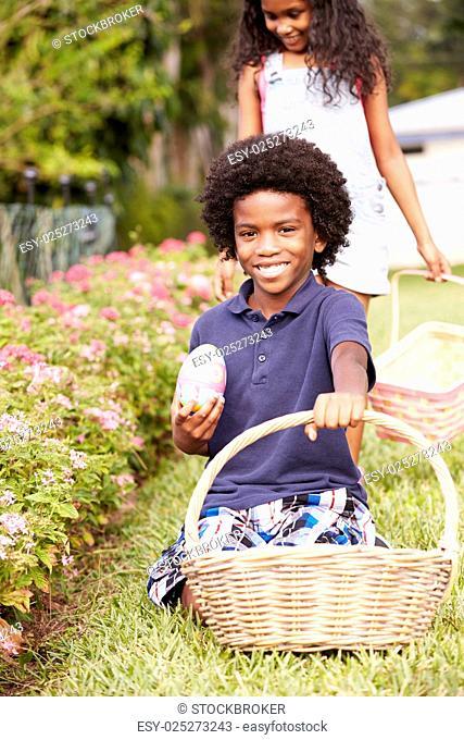 Two Children On Easter Egg Hunt In Garden