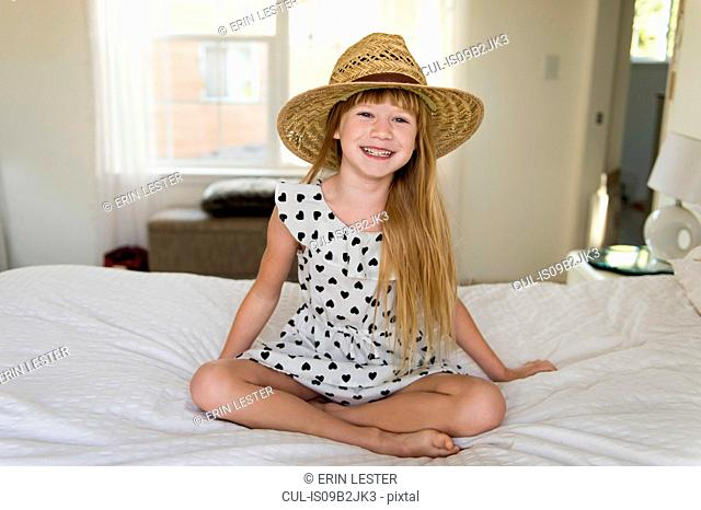 Young girl sitting on bed smiling, wearing straw hat