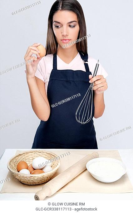 Woman holding an egg and wire whisk and thinking