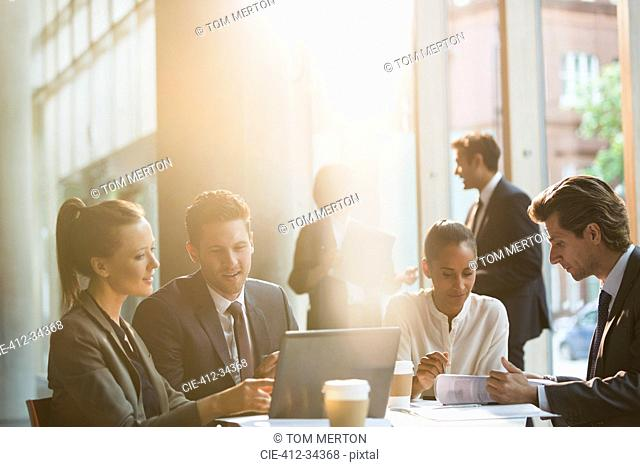 Business people working at laptop and reviewing paperwork in meeting