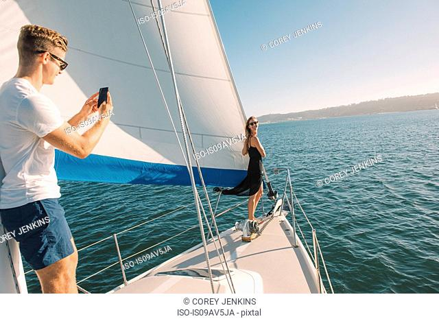 Couple taking photograph on sailboat, San Diego Bay, California, USA