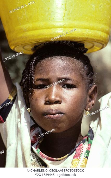 Niger  Fulani Girl Carrying Water on Head  Note head cloth, which serves as a cushion