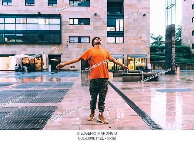 Man welcoming rain in town square, Milan, Italy