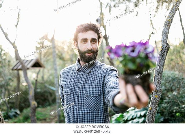 Man holding a flower in garden