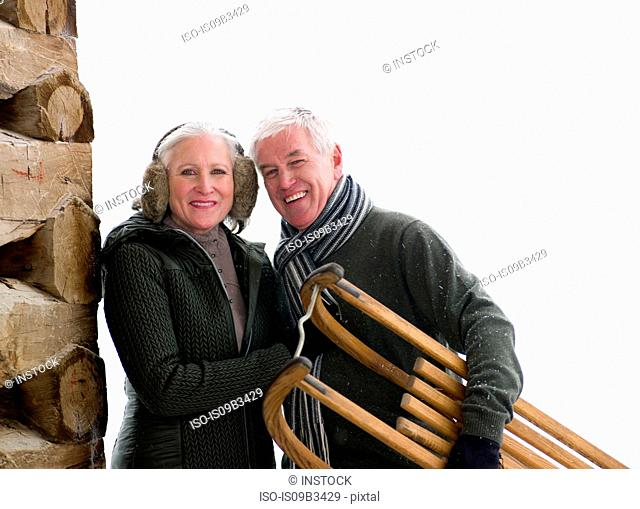 Portrait of couple standing outside cabin in snow carrying toboggan, Colorado, USA