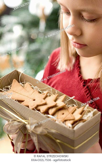 girl with a box full of christmas cookies
