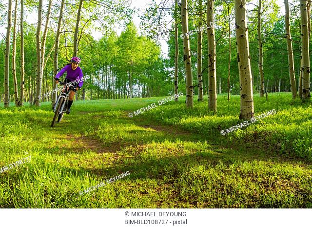 Hispanic teenager riding bicycle in woods