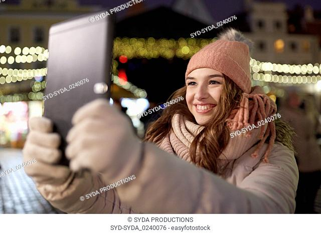 woman with tablet pc at christmas tree outdoors