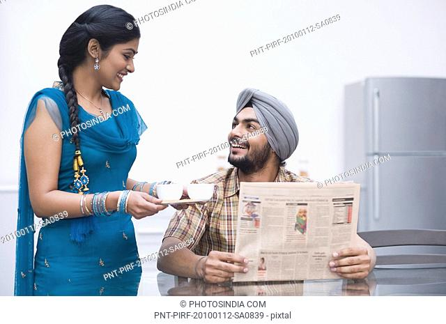 Man reading a newspaper with his wife serving tea