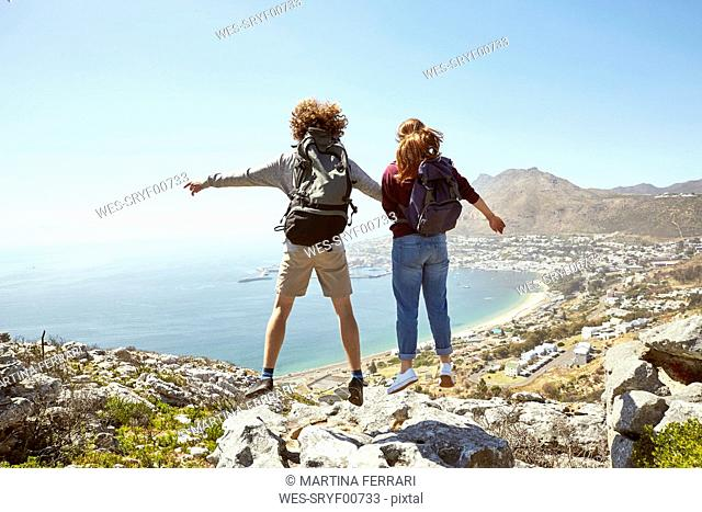 South Africa, Cape Town, young couple jumping on a trip at the coast