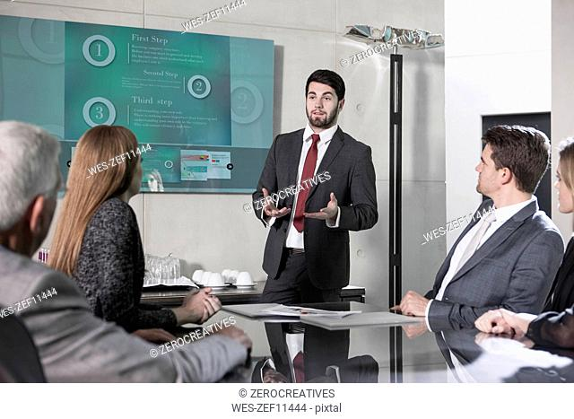 Businessman holding presentation in front of team