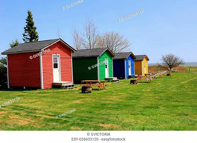 Colorful one room shacks or cabins with picnic tables and fire pits near the ocean in St. Martins New Brunswick, Canada