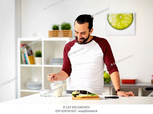 vegetarian food, healthy eating, people and diet concept - man adding sugar to tea or coffee cup and having vegetable sandwiches for breakfast at home kitchen