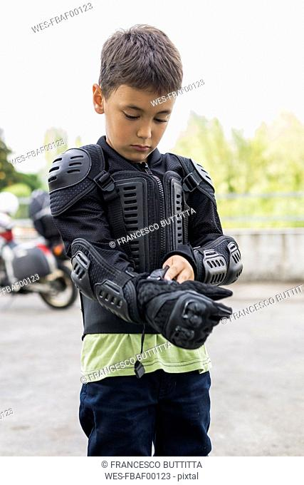 Boy putting on protective clothing preparing for a motorbike trip