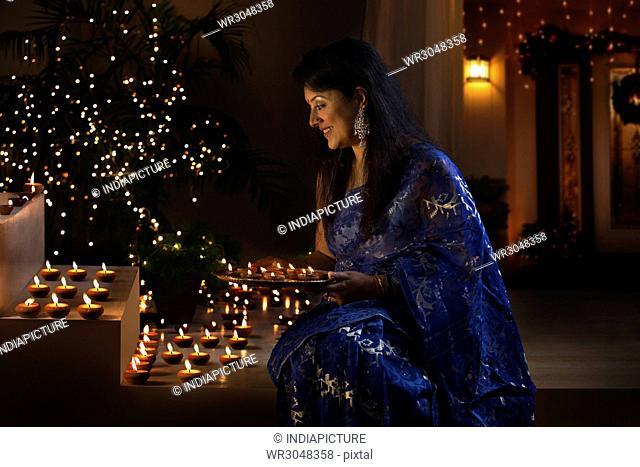 Woman arranging oil lamps at a diwali festival