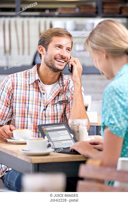 Smiling couple with digital tablet and cell phone in coffee shop