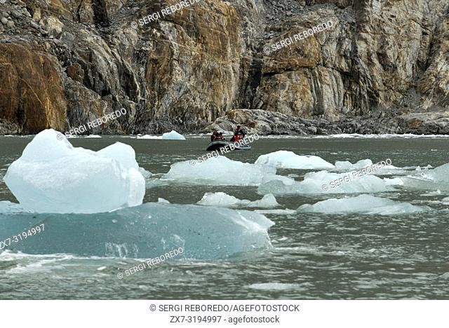 Safari Endeavour cruise passengers in an inflatable boat in front of Dawes Glacier calves into the Endicott Arm fjord of Tracy Arm in Fords Terror Wilderness