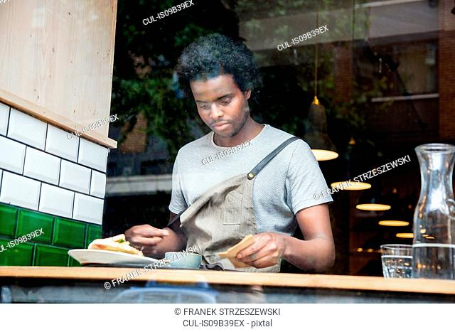 Waiter preparing order at cafe window