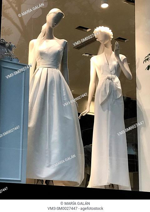 Two mannequins wearing wedding dresses in a shop window. Madrid, Spain