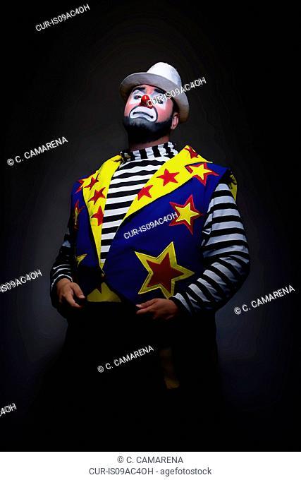 Studio portrait of clown with hands in pockets