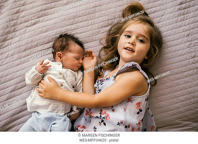 Smiling girl lying on blanket cuddling with her baby brother