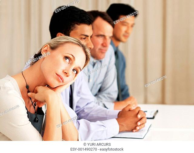 Beautiful Caucasian business woman daydreaming while attending board meeting with colleagues