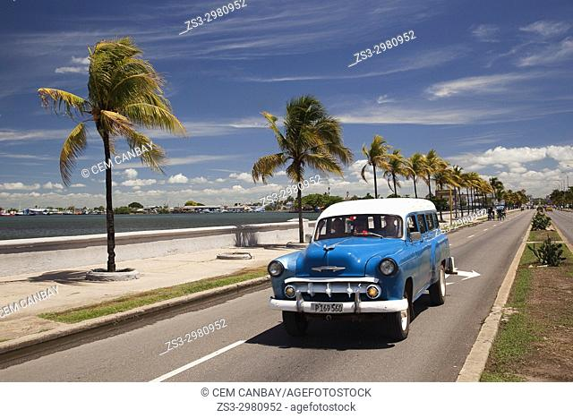 Old American car by the water promenade Malecon at Punta Gorda district, Cienfuegos, Cuba, West Indies, Central America