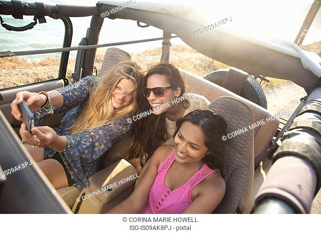 Three young women taking selfie on smartphone in jeep at coast, Malibu, California, USA