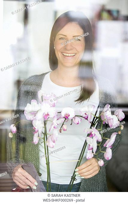 Woman with orchid looking through windowpane