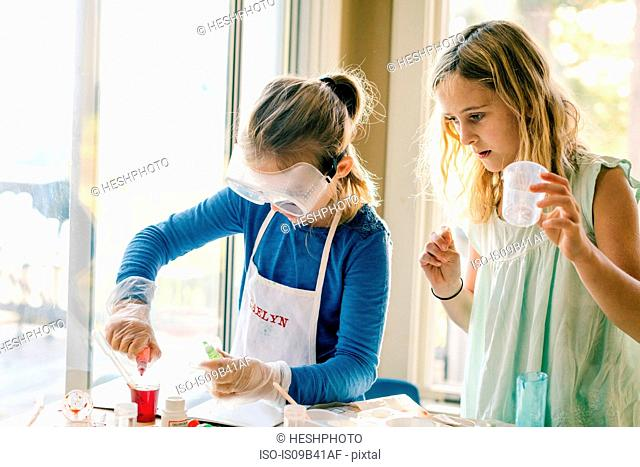 Two girls doing science experiment, with red liquid