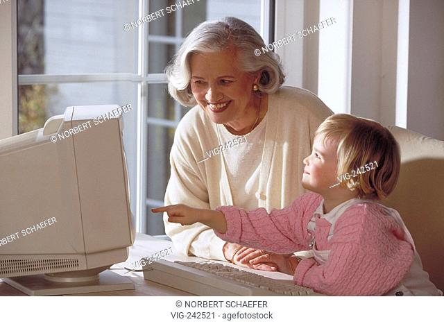 indoor, blond girl sits with her grandmother at the table near the window showing her something in the computer  - GERMANY, 26/02/2005