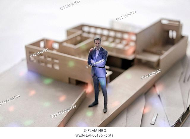 Miniature businessman figurine standing in architectural model with points of light