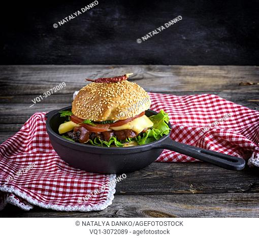 burger with a meatball and vegetables in a black round cast-iron frying pan, copy space