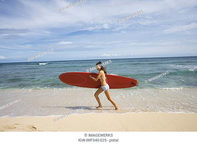 Portrait of a young woman running on beach