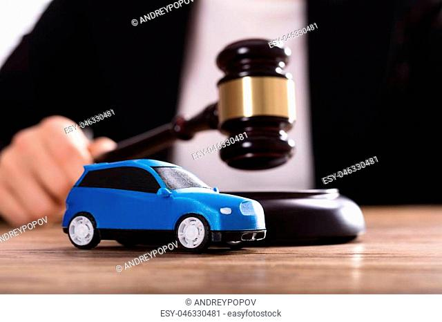 Close-up Of A Small Blue Car In Front Of Judge Holding Mallet