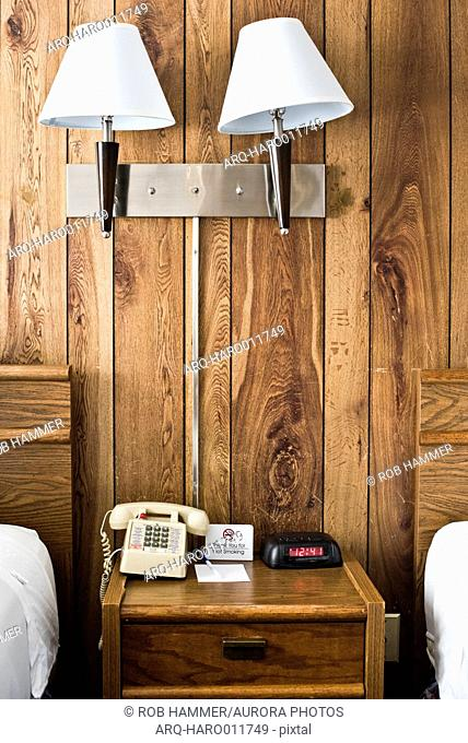 View of night table in hotel with telephone and alarm clock against wooden wall